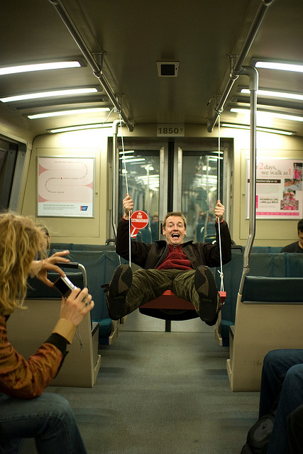 A man swings through the aisle of a train.